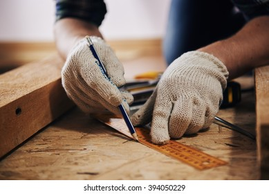 Woodworker with lumber. Professional builder evaluating size of workbench with pencil and ruler.