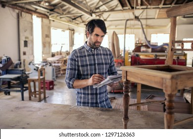 Woodworker standing by a chair on a workbench in his carpentry workshop reading over designs in a notebook