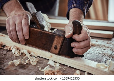 Woodworker using a plane to smooth down the surface of a plank of lumber on his workbench in a close up view on his hands with sawdust and fresh shavings