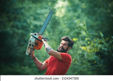 Woodworkers lumberjack. Lumberjack on serious face carries chainsaw. Man doing mans job. Lumberjack worker walking in the forest with chainsaw