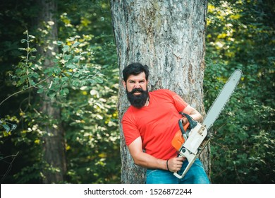 Woodworkers lumberjack. Stylish young man posing like lumberjack. Lumberjack worker walking in the forest with chainsaw. Lumberjack holding the chainsaw