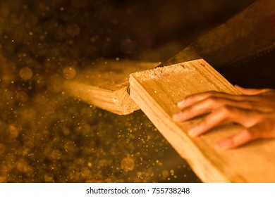 Woodworking with a handsaw and sawdust in the air