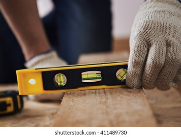 Woodworking. Male joiner in gloves measuring timber with plane on the floor.