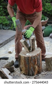 woodworking man with a splitting wedge, preparing firewood in the garden