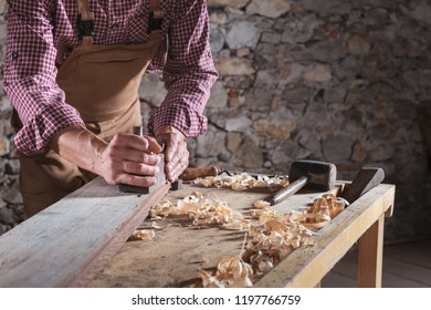 Woodworking man wearing brown work overalls scraping plank while it sits on wooden workbench with other tools nearby