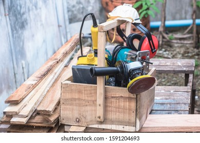 Woodworking power tools including rectangular orbit sander, grinder and jig saw with wooden tool box at outdoor workshop.