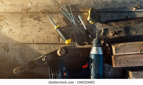 woodworking tools lying on a rough wooden table flat top view