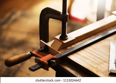 Woodworking. Wood working project on work bench, with c-clamps and bar clamp. Focus on jaw section of clamp.  Shallow depth of field.