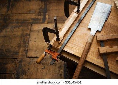 Woodworking. Wood working project on work bench, in a workshop with wooden floor. Clamped pieces of wood with c-clamps and bar clamp. shot in low key and shallow depth of field.