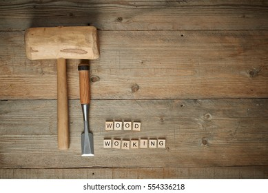 woodworking word with mallet and chisel on a wooden workbench, top view