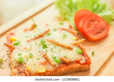 Woodworm, Edible insects with carrots, peas, corn, mozzarella cheese, sliced bread. Insect food is the healthy meal high protein popular food in Thailand. Closeup, Selective focus