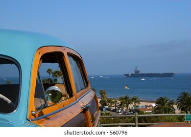A woody retro classic car with the USS Ronald Reagan in the background in Santa Barbara, California.