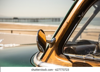 woody surf classic car in california at the beach with pier summer