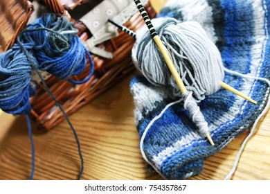 wool and knitting needles basket on a wooden background