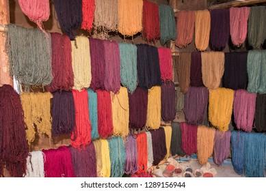 Wool in multiple colors hanging on drying racks with dye bowls below