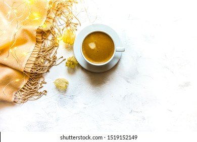 Wool pashmina shawl, cup of hot expresso coffee, dried physalis skeletons, and fairy lights on a white background.  Top view. Staying warm in fall concept.