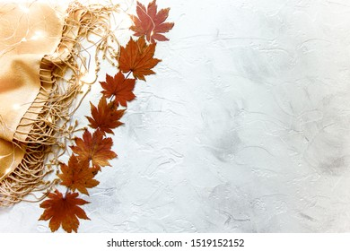 Wool pashmina shawl, red maple leaves, and fairy lights on a white background.  Top view. Staying warm in fall concept.