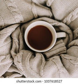 Wool sweater, knitted plaid and coffee cup. Breakfast in bed. Sweet home. flat lay, still life