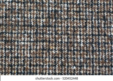 Wool or Tweed texture background. Fabric  checkered in brown. Houndstooth texture.