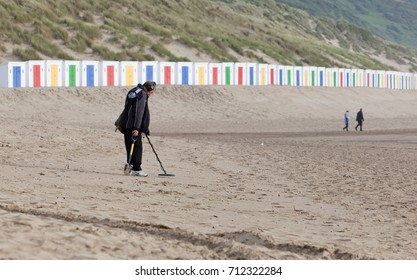 WOOLACOMBE, UK - MAY 18, 2011: Man uses a metal detector on Woolacombe beach, with brightly coloured beach huts and 2 other people out-of-focus in the background.