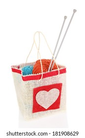 Woolen balls of yarn and wooden knitting needles in rustic craft bag, isolated on white