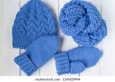 The woolen blue yarn ball. The knitted hat, mittens and scarf. The wooden white background.