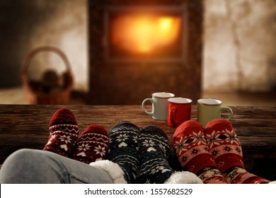 Woolen christmas socks and woman legs on wooden table. Free space for your decoration.Fireplace in home interior with warm orange light of fire.Copy space and winter cold night.Xmas time and gifts.