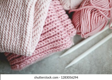 Woolen pink yarn and a knitting needles. Home hobbies, cozy knitted sweaters