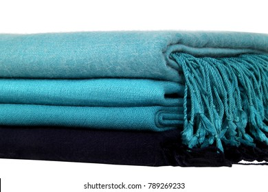 Woolen shawls/stoles folded and arranged into a stack of four rows. The beautiful texture and colors of the shawls create amazing effect. The end point threads are displayed beautifully .