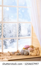 Woolen yarn and fabric on the window sill. Beautiful view outside the window - winter landscape and snow.