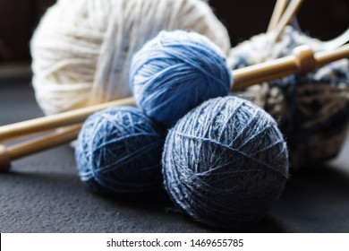 Woolen yarn for knitting. Close-up shots of white and blue balls of natural wool yarn and wooden knitting needles