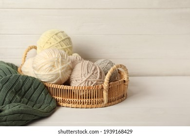 Woolen yarns in basket on white wooden table. Space for text