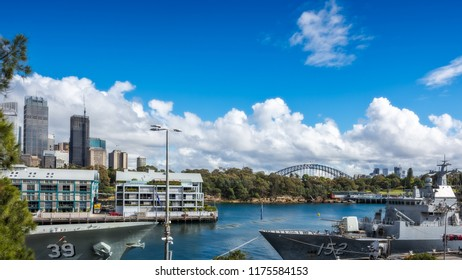 Woolloomooloo Bay, Sydney, Australia -September 03, 2018: Woolloomoolo Bay Wharf with Royal Australian Navy ships in the foreground and Sydney Skyline in the background on a beautiful sunny morning.
