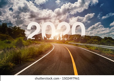 The word 2020 behind the tree of empty asphalt road at golden sunset and beautiful blue sky. Concept for vision year 2020.