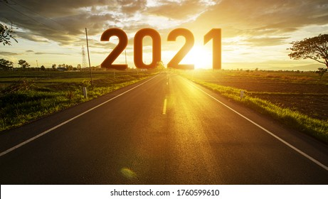 The word 2021 behind the tree of empty asphalt road at golden sunset and beautiful blue sky. Concept for vision year 2021.