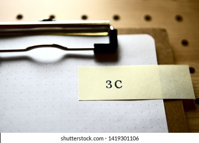 """The word """"3C"""" stamped yellow slip on clipboard. In level angle."""