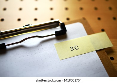 """The word """"3C"""" stamped yellow slip on clipboard. In diagonal angle."""