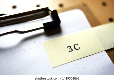 """The word """"3C"""" stamped yellow slip on clipboard. In diagonal angle. Close up."""