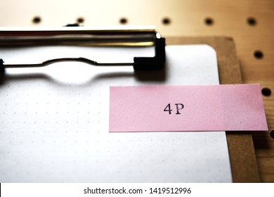 """The word """"4P"""" stamped pink slip on clipboard. In level angle. It means Product, Price, Promotion, Place."""