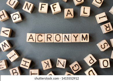 the word acronym wooden cubes with burnt letters, use of acronyms in the modern world, gray background top view, scattered cubes around random letters
