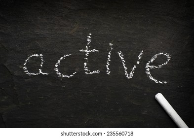 The word active written with chalk on black stone.