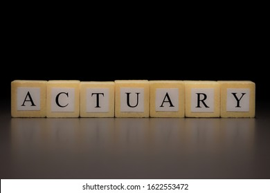 The word ACTUARY written on wooden cubes isolated on a black background