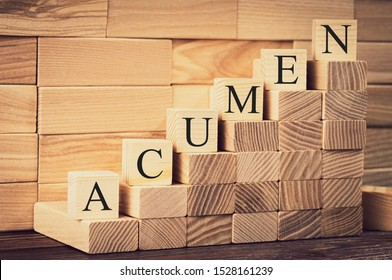 the word of acumen is made with building blocks on a wooden background, vignetting and toning the image, selective focusing