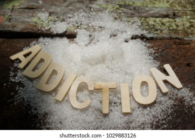Word ADDICTION and sugar on wooden background. Sugar can cause addiction.