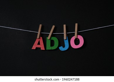 Word Adjo on black background. Adjo means good bye in Swedish . Concept for art, learning, and education.