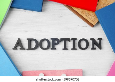 Word ADOPTION and notepads on wooden background