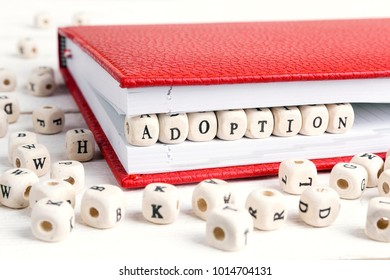 Word Adoption written in wooden blocks in red notebook on white wooden table.