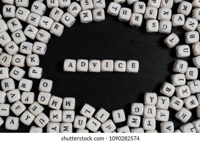 Word ADVICE on wooden cubes on a black wooden table with copy space