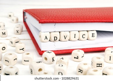 Word Advice written in wooden blocks in red notebook on white wooden table. Wooden abc.