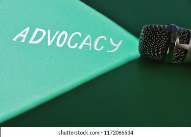 Word advocacy written on a greenish background in the beam of light, microphone laying down on a shady side. Conceptual photography.